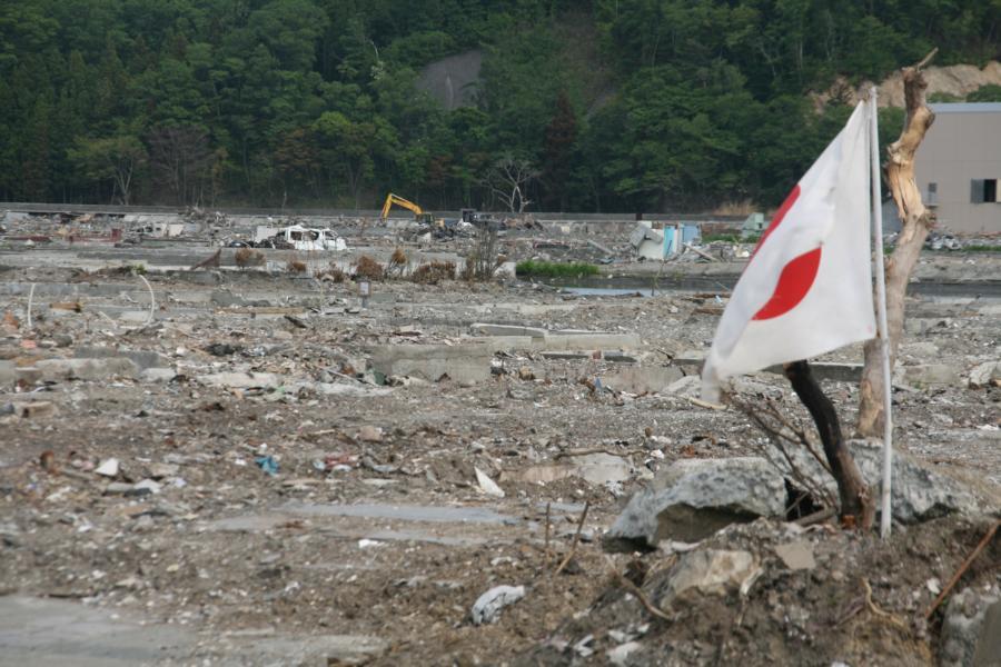 Bandera de Japón en un campo destrozado por el tsunami